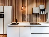 Kochen und Arbeiten mitten im Wald: Die mit Abstand angebrachten Holzlamellen sorgen für eine sanfte räumliche Trennung zwischen Küche und Büro.